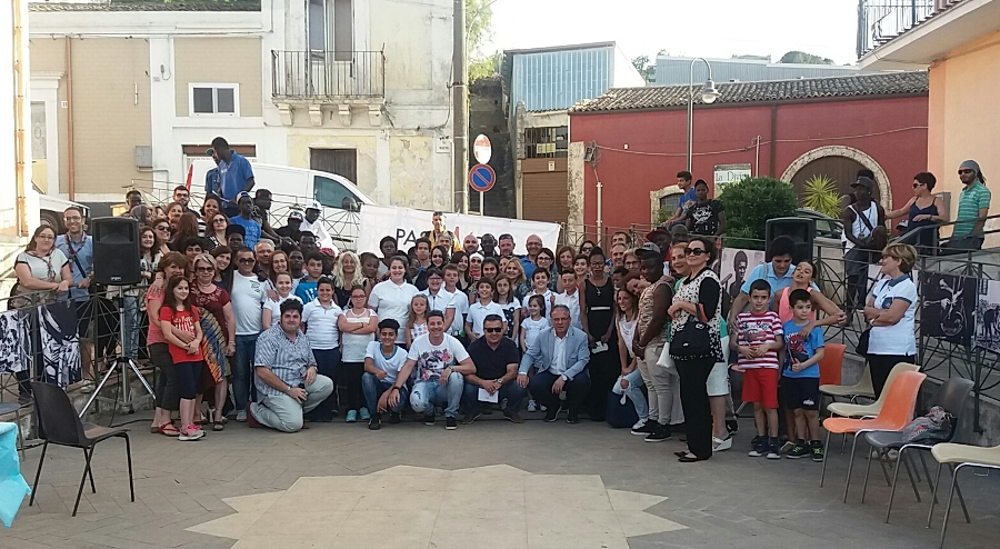 Foto di gruppo in Piazzetta San Giovannni con il sindaco, amministratori, operatori, rifugiati, volontari e cittadini